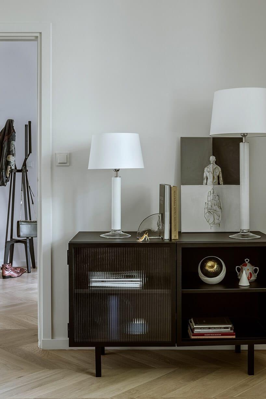 ciemno brązowa komódka zprzeszklenie oraz białymi lampami iobrazem zręka oraz postura człowieka