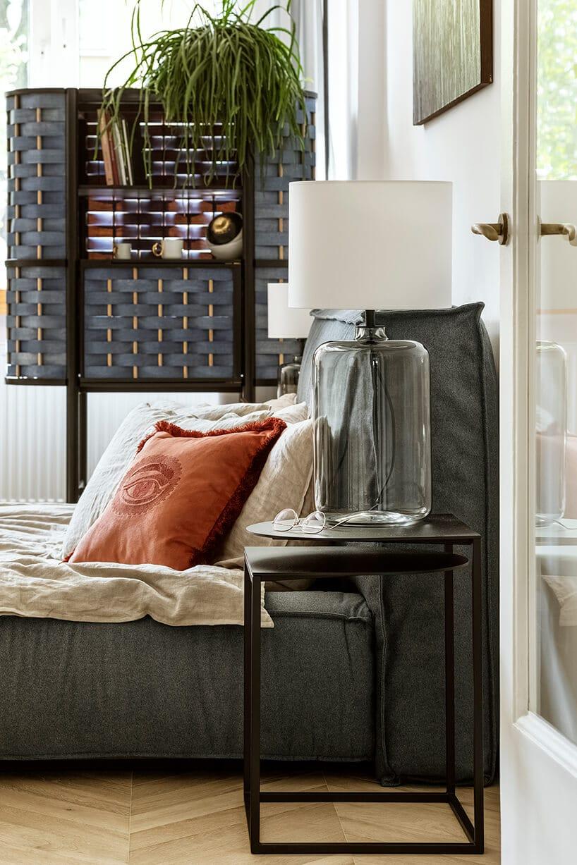 szare materiałowe łóżko zczerwoną poduszką zokiem oraz małym stoliczek obok zlampo-wazonem