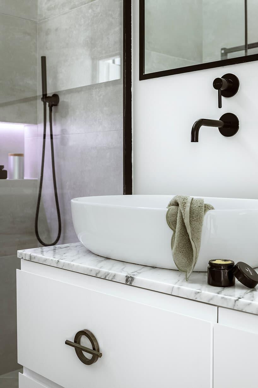 szafka umywalkowa zblatem marmurowym oraz złotą klameczka