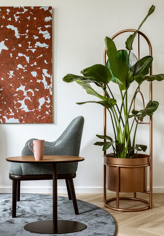 duży zielony kwiat wspecjalnej doniczce przy szarym fotelu zczarnymi nogami
