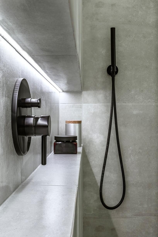 łazienka wkaflach imitujących surowy beton zzaworem wodnym wczarnym macie