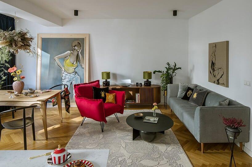 nowoczesne wnętrze zczerwonym fotelem iszara kanapą na drewnianej podłodze