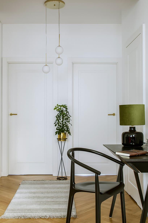 biała ściana zwtopionymi białymi drzwiami przy drewnianej podłodze