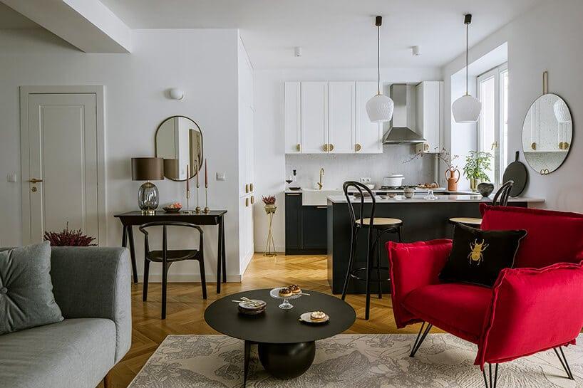 czerwony fotele zchromowanymi nóżkami zpochyleniem na dywanie przy stoliku kawowym