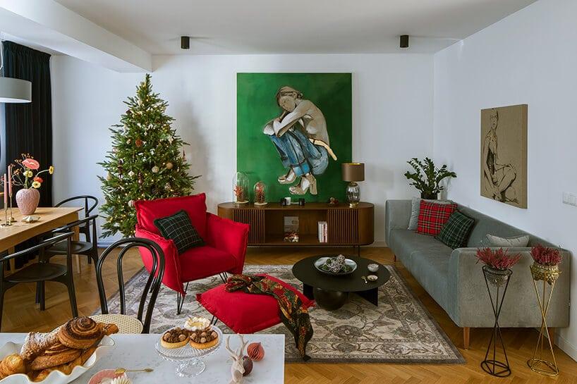 wnętrze salonu zchoinką oraz dużym zielonym obrazem na ścianie