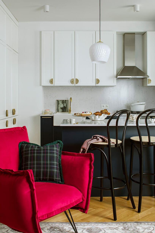 czerwony duży fotel na tle czarnej kuchni ikrzeseł barowych