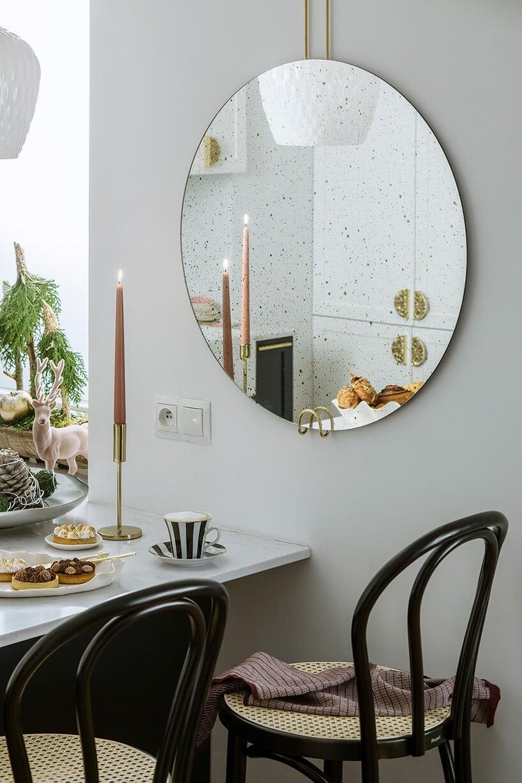 czarne krzesła barowe przy lekko szarej ścianie zokrągłym lustrze