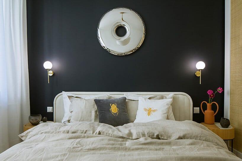 sypialnia zbiałą pościelą oraz poduszkami na tle czarnej ściany