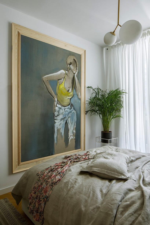 sypialnia zdużym obrazem wbrązowej ramie obok zielonej rośliny