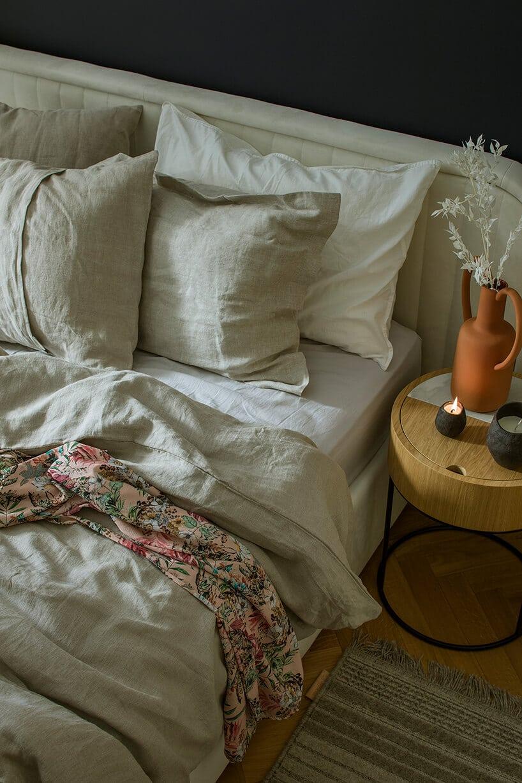 drewniany stolik nocny zszufladą obok łóżka