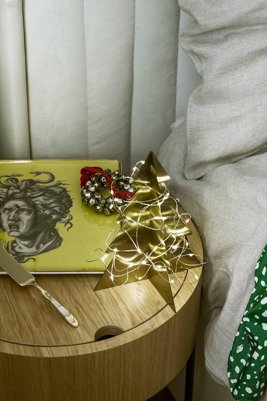 okrągły stolik zdrewna ze złotymi dekoracjami przy łóżku