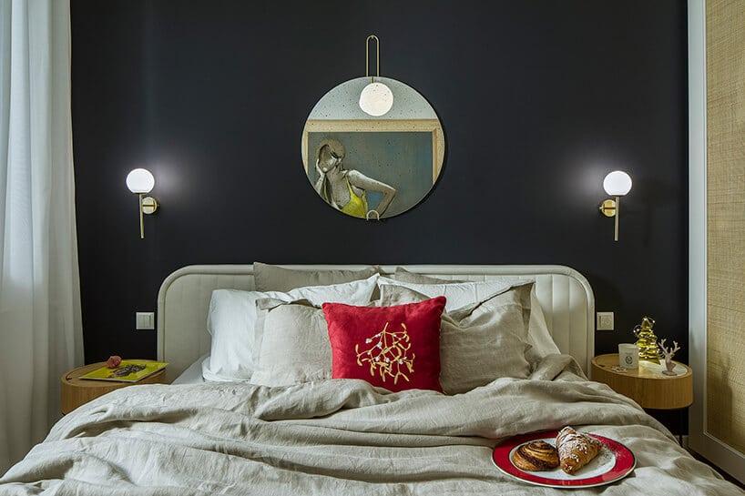 duże łóżko zzagłówkiem oraz centralnie położoną czerwoną poduszką pod lustrem na czarnej ścianie