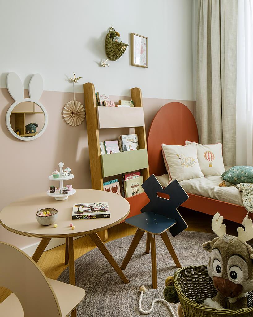 drewniany niskie stolik na szeroko rozstawionych nogach wdziecięcym pokoju zzabawkami iczerwonym łóżkiem