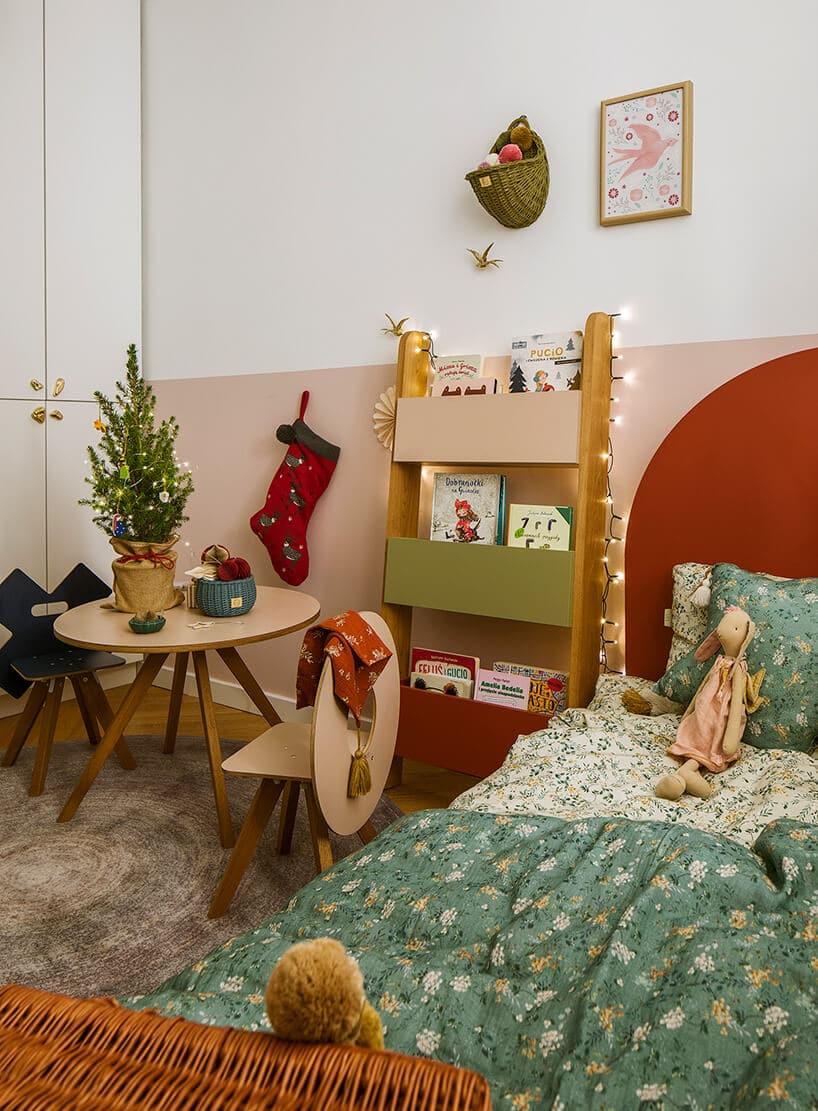 pastelowe kolory wdziecięcym pokoju zczerwonym łóżkiem zzieloną pościelą