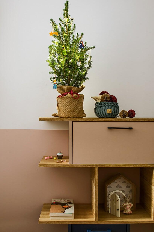 ściana zkoloru białego oraz różowego przy komodzie zzieloną choinką