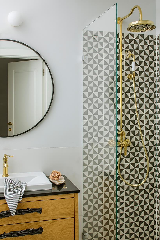 okrągłe lustro nad umywalką oraz czarno dębową szafką obok szyby
