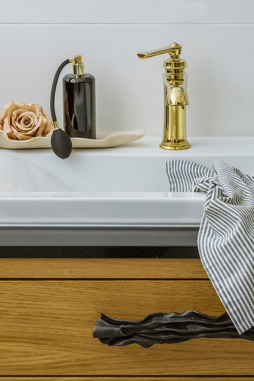 złota bateria umywalkowa obok zbiornika zpompką wformie gruszki