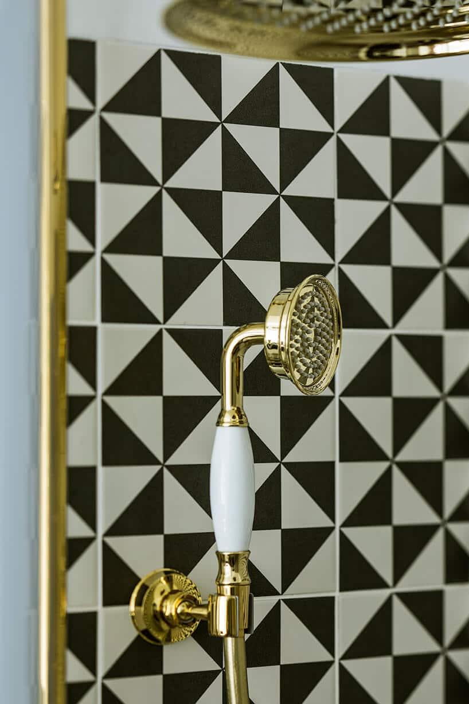 czarno-białe trójkąty na ścianie za złotym prysznicem ze białą rączką