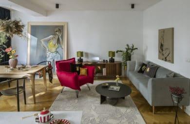 nowoczesne wnętrze z czerwonym fotelem i szara kanapą na drewnianej podłodze