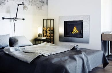 elegancki kominek w białej ścianie jasnego salonu obudowany szczotkowanym metalem