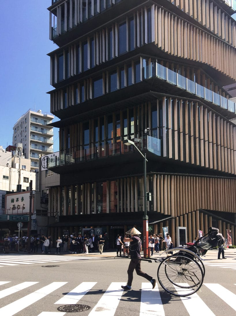 wysoki budynek przy jednym ze skrzyżowań wjapońskim mieście zdrewnianą elewacją