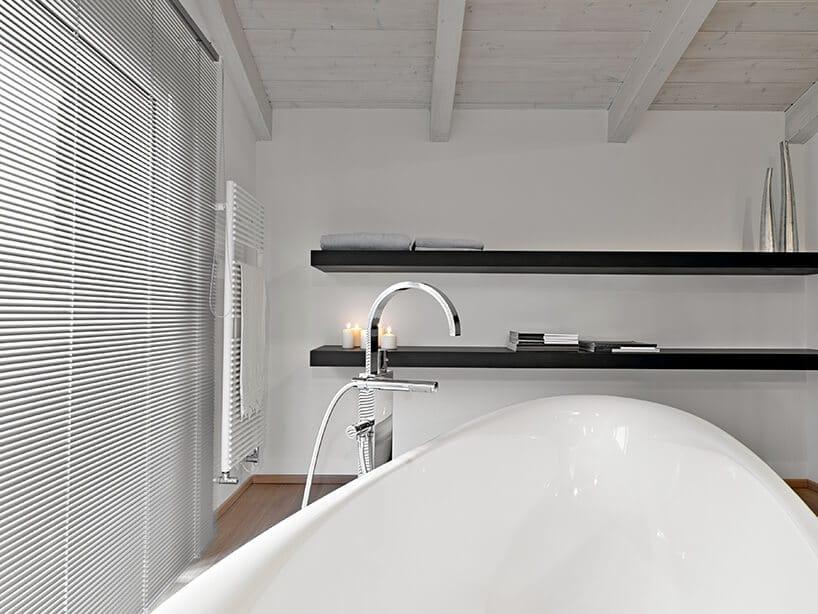biała wanna zchromowanym wolnostojącym kranem obok wdużym pokoju kąpielowym