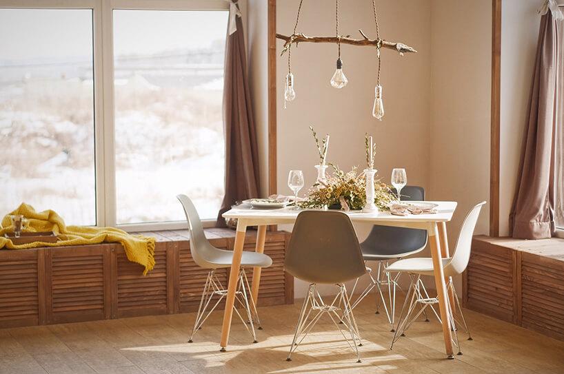 elegancka mała jadalnia zdrewnianym stołem zczterema krzesłami pod żyrandolem zdrewnianego patyka
