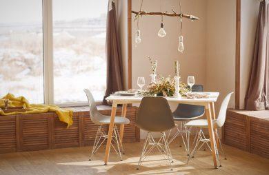 elegancka mała jadalnia z drewnianym stołem z czterema krzesłami pod żyrandolem z drewnianego patyka