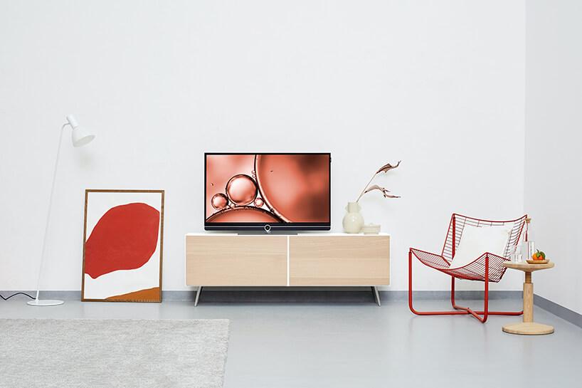 elegancki telewizor zczarną ramką na białej szafce rtv zdrewnianymi jasnymi frontami