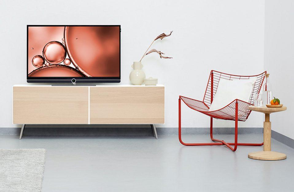 elegancki telewizor z czarną ramką na białej szafce rtv z drewnianymi jasnymi frontami