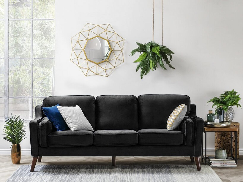 rama do lustra przypominająca złote promienie słoneczne na czarną sofą
