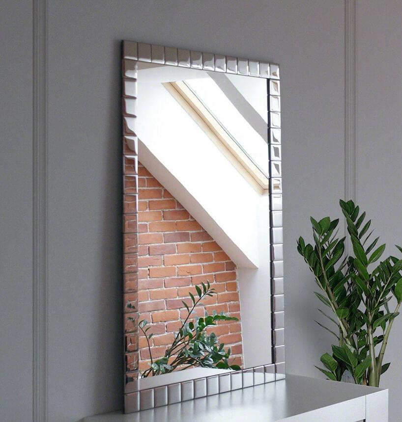 lustro stojące na szarej szafce zramą do lustra srebrne kwadraty