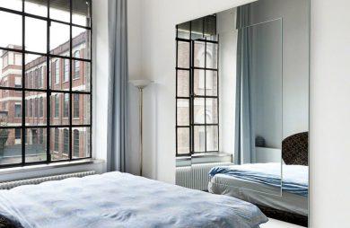 rama do lustra z lustra w sypialni z dużymi pofabrycznymi oknami