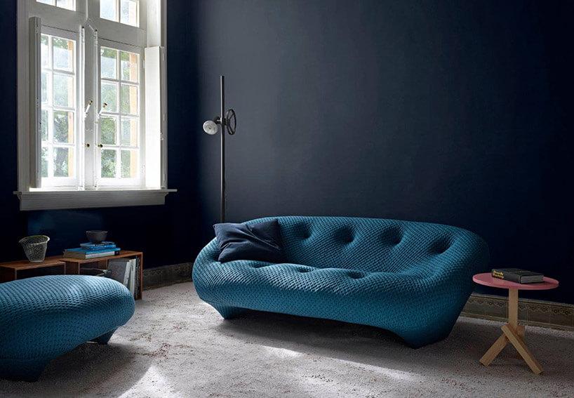 niebieska sofa na tle czarnej ściany