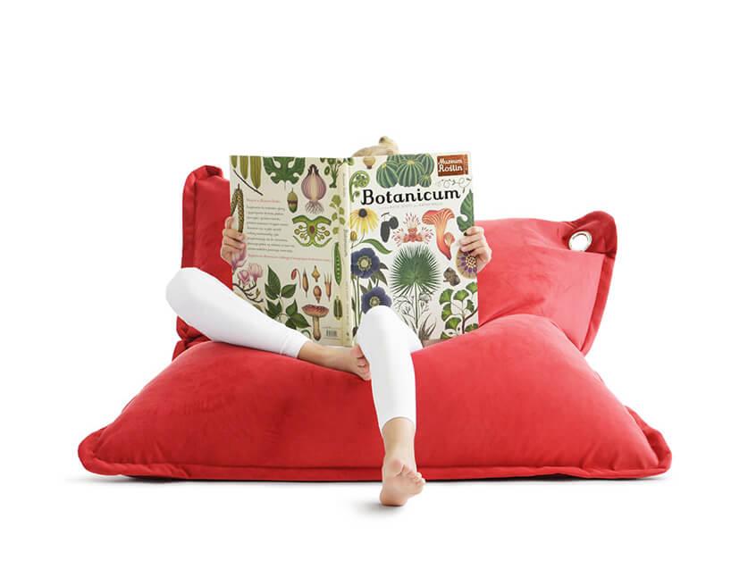 dziecko czytające książkę na czerwonej poduszce