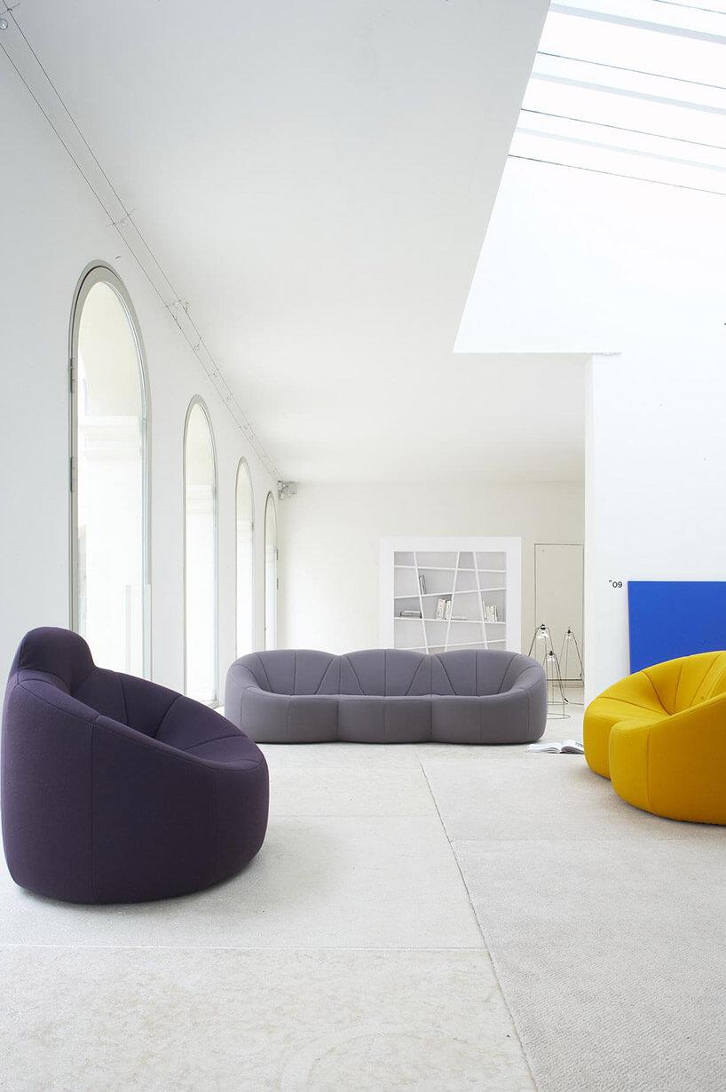 kolorowe sofy ifotel wbiałym wnętzrzu