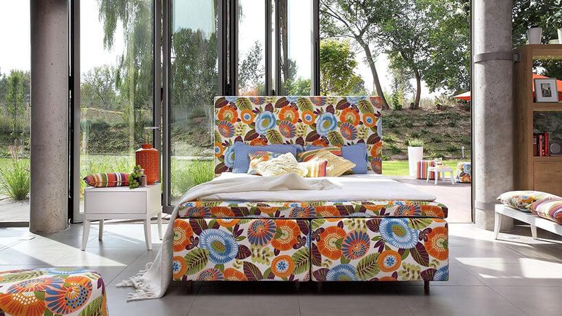 duże łóżko ztapicerką wwielkie kolorowe kwiaty