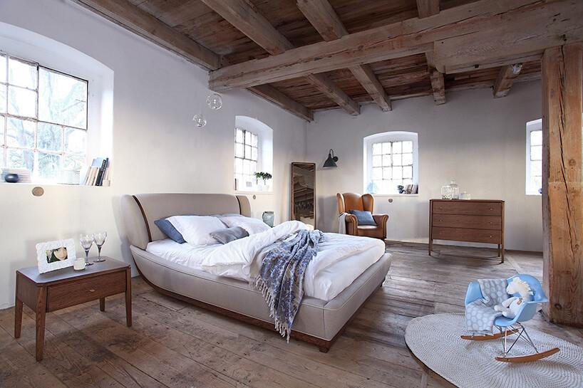 ładnie zaaranżowana duża sypialnia znietypowym brązowym sufitem
