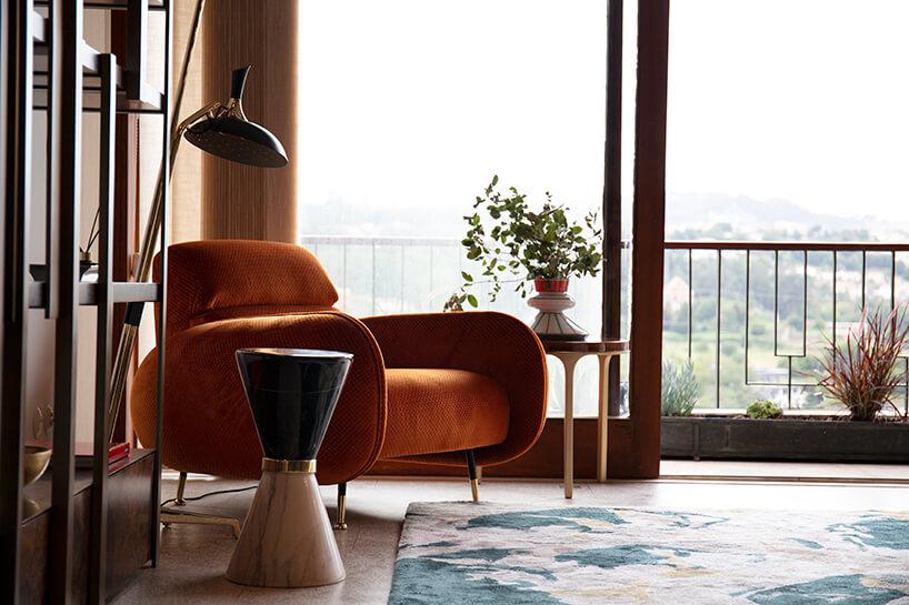 wnętrze wyjątkowego showroom covet valley elegancki pomarańczowy fotel zniskim oparciem obok wyjątkowego stolika wkształcie klepsydry ze złotą opaską