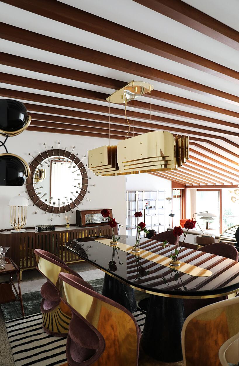wnętrze wyjątkowego showroom covet valley ciemny błyszczący stół ze złota wstaką na złoconą wyjątkową lampą