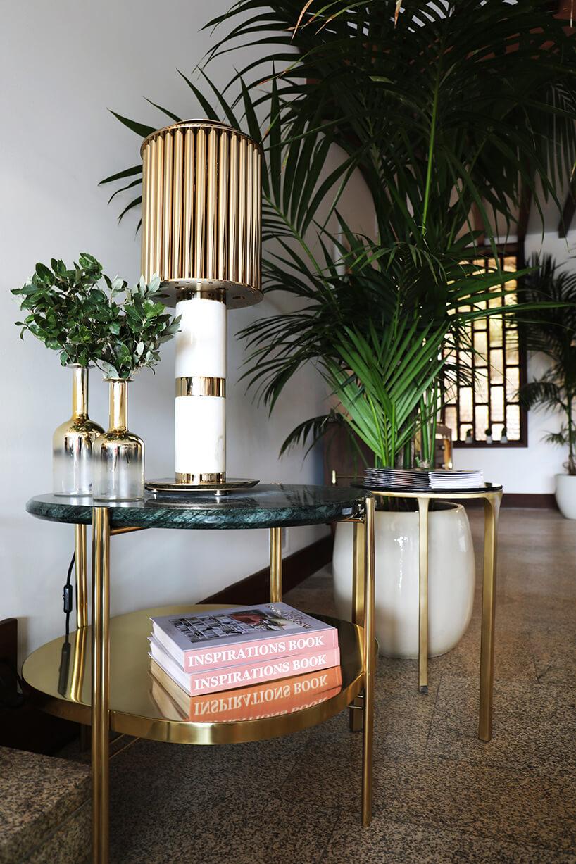 wnętrze wyjątkowego showroom covet valley elegancki mały okrągły stolik zzielonym kamiennym blatem na złotym stelażu