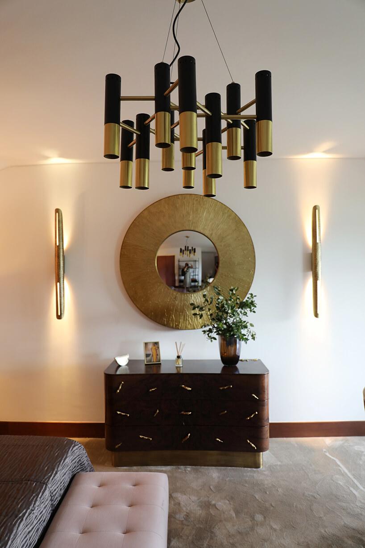 wnętrze wyjątkowego showroom covet valley elegancka ciemno brązowa komoda pod lustrem zgrubym złotym obramowanie pod czarno brązowy żyrandolem