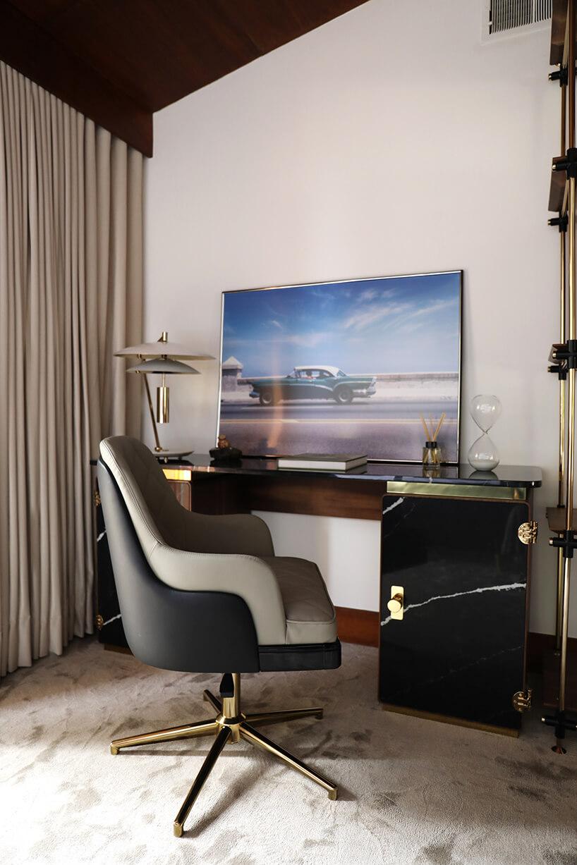wnętrze wyjątkowego showroom covet valley elegancki szaro czarny fotel na złotej nodze przy brązowym eleganckim biurku zkamiennym frontem ze złotymi akcentami