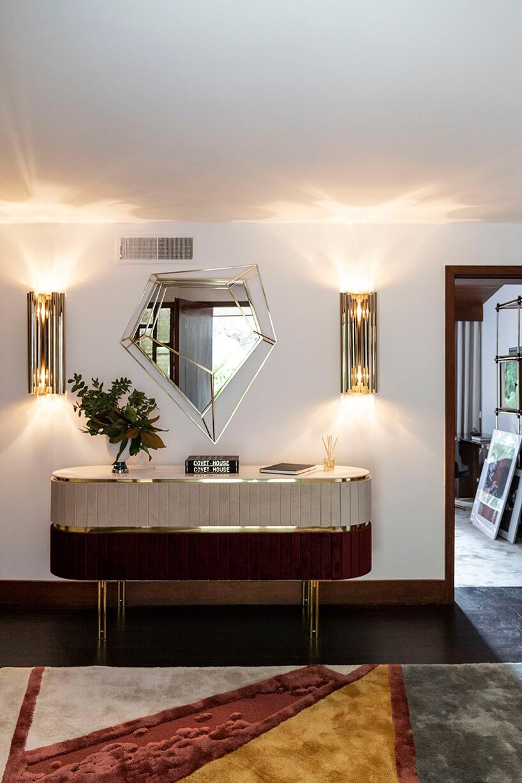 wnętrze wyjątkowego showroom covet valley elegancka biało brązowa komoda na wysokich złotych nogach pod eleganckim lustrem pomiędzy dwoma złotymi lampami