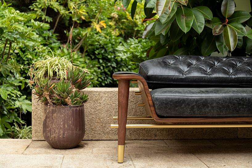 wnętrze wyjątkowego showroom covet valley elegancka sofa zczarnym siedziskiem drewnianym stelażu ze złotymi akcentami