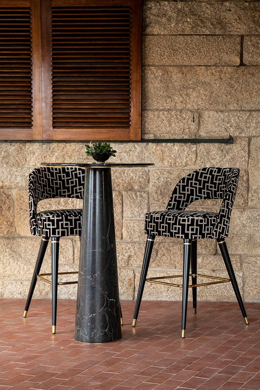 wnętrze wyjątkowego showroom covet valley dwa czarne wysokie krzesła zbiałym wzorem na tle kamiennej zewnętrznej ściany