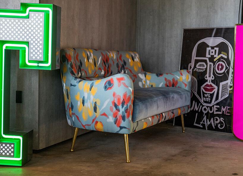 wnętrze wyjątkowego showroom covet valley niebieska sofa zkolorowymi plamami przy nwooczesnym plakacie pomiędzy neonami