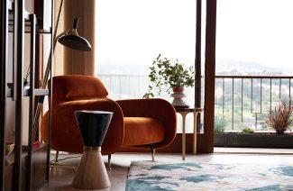 wnętrze wyjątkowego showroom covet valley elegancki pomarańczowy fotel z niskim oparciem obok wyjątkowego stolika w kształcie klepsydry ze złotą opaską