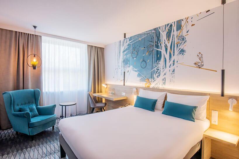 ibis Styles Santorini pokój hotelowy złóżkiem iniebieskimi poduszkami