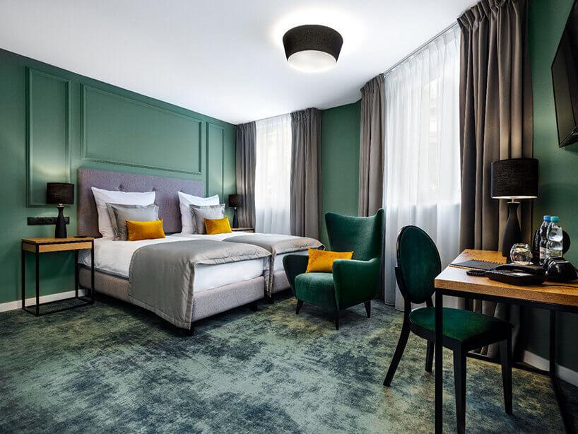 Wawel Queen pokój hotelowy zzielonymi ścianami , zielonym fotelem iżółtymi poduszkami